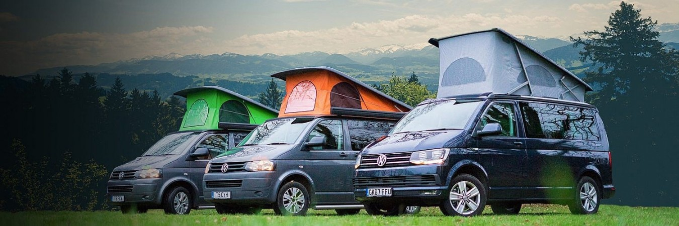 3 of Call Campervan Hire's camper vans against a mountain background